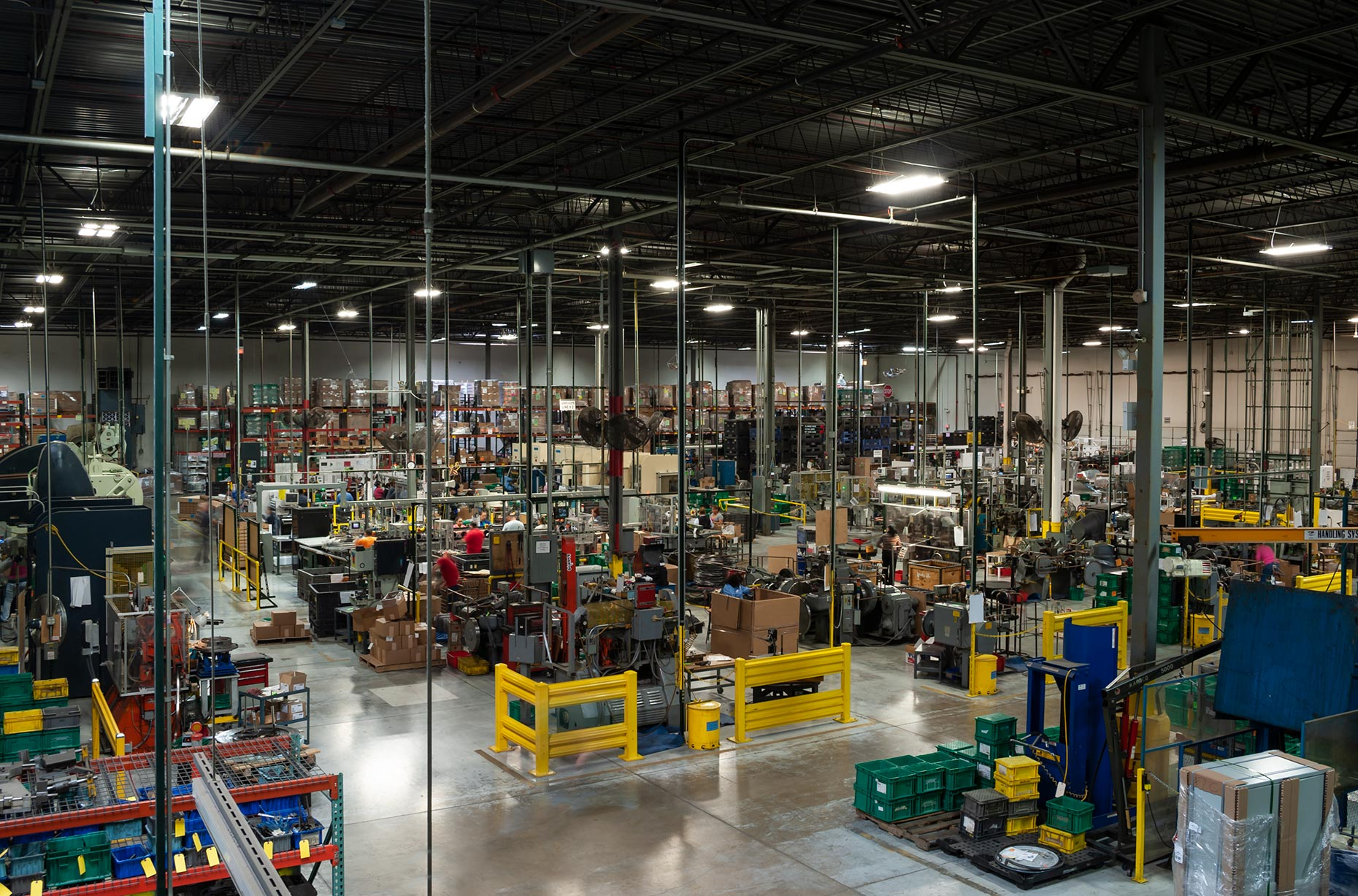 Panoramic view of manufacturing plant warehouse filled with machinery and packaging